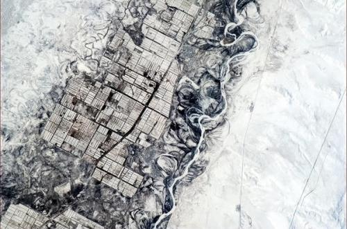 Humans need straight lines, nature doesn't. Indecisive river and orderly farmers, central Asia.