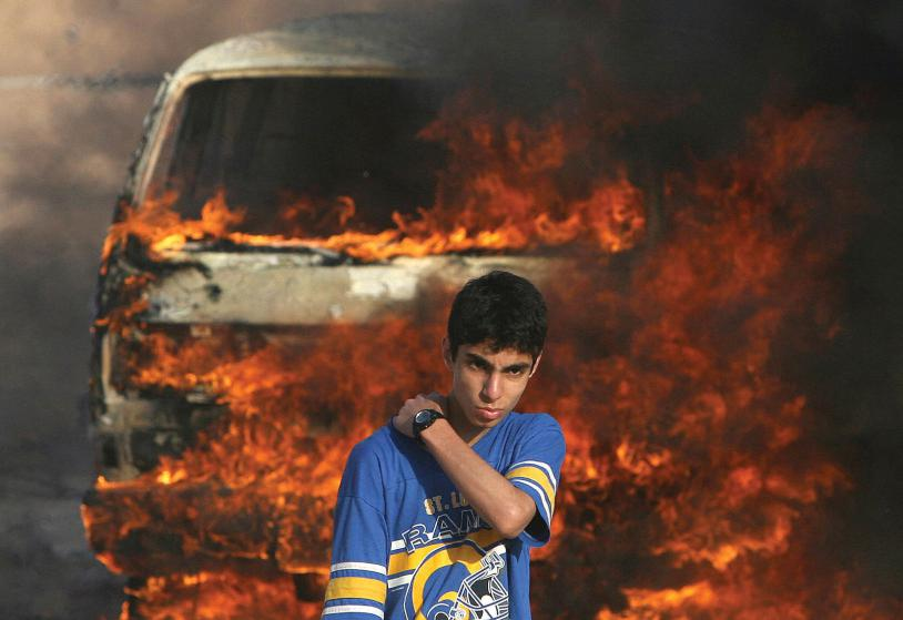GAZA CITY, -: A Palestinian youth stands in front of a burning vehicle during clashes between rival Fatah and Hamas in Gaza City, 14 May 2007. Two Palestinians were killed in fresh fighting between rival Fatah and Hamas gunmen today despite a truce aimed at ending the worst factional violence since a unity government took office. MOHAMMED ABED/AFP/Getty Images